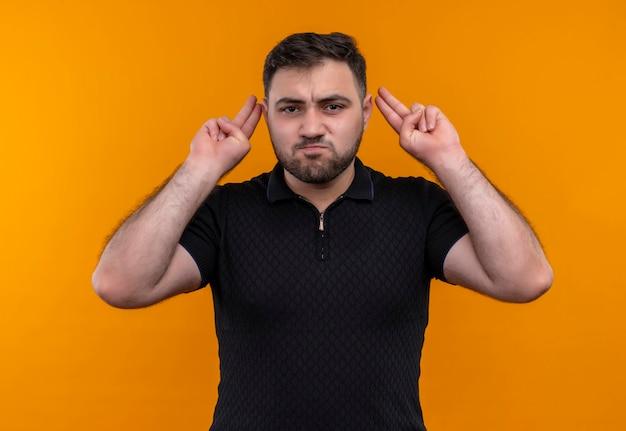Junger bärtiger mann im schwarzen hemd, das kamera mit wütendem gesicht betrachtet, das mit händen gestikuliert
