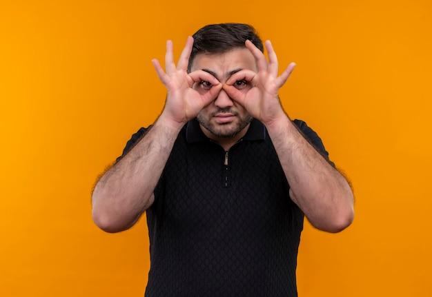 Junger bärtiger mann im schwarzen hemd, das ok zeichen mit fingern wie fernglas tut, das durch finger schaut