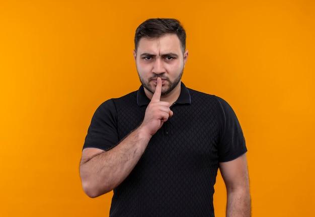 Junger bärtiger mann im schwarzen hemd, das schweigengeste mit dem finger auf den lippen macht, die kamera mit stirnrunzelndem gesicht betrachten