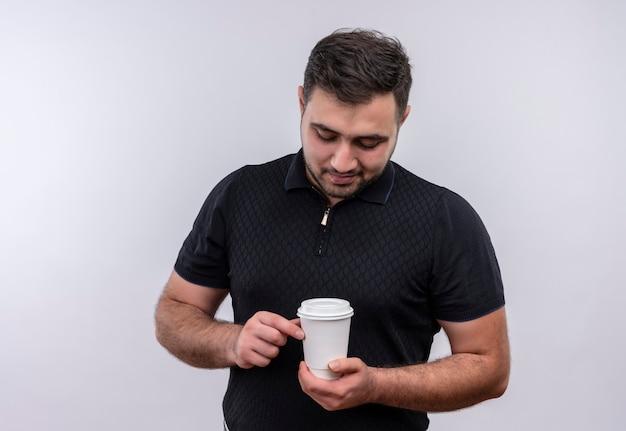 Junger bärtiger mann im schwarzen hemd, der kaffeekappe hält, die es mit lächeln auf gesicht betrachtet