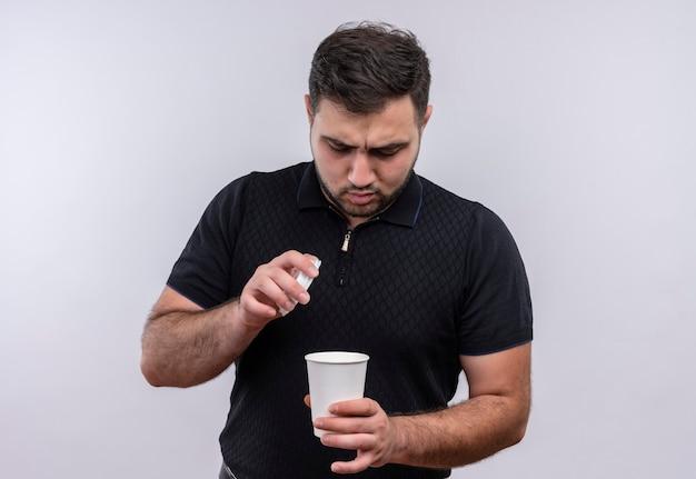 Junger bärtiger mann im schwarzen hemd, der kaffeetasse hält, die es mit ernstem gesicht betrachtet
