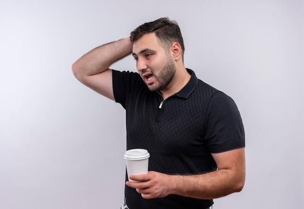Junger bärtiger mann im schwarzen hemd, der kaffeetasse hält, die mit nachdenklichem ausdruck auf gesicht verwirrt betrachtet