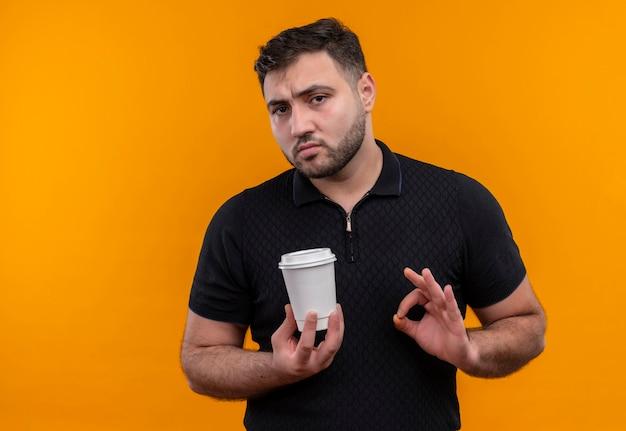Junger bärtiger mann im schwarzen hemd, der kaffeetasse hält ok zeichen, das zuversichtlich schaut