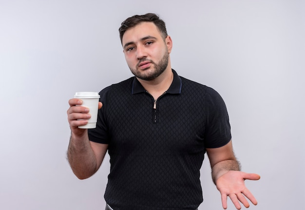Junger bärtiger mann im schwarzen hemd, der kaffeetasse hält und verwirrt schaut