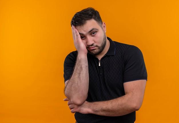 Junger bärtiger mann im schwarzen hemd, der kamera betrachtet, der kopf auf arm gelangweilt und müde lehnt