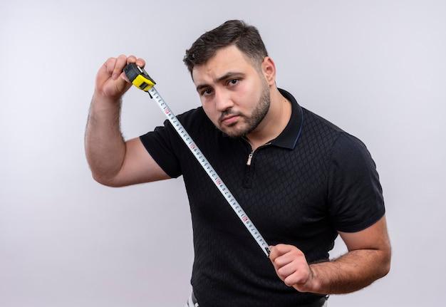 Junger bärtiger mann im schwarzen hemd, der maßband hält kamera mit ernstem gesicht betrachtet
