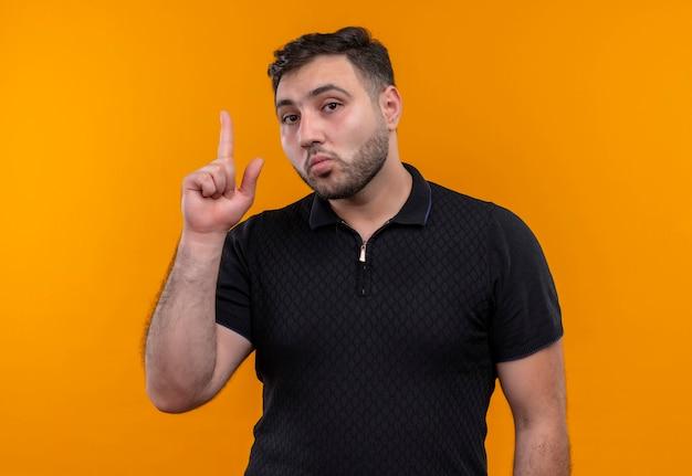 Junger bärtiger mann im schwarzen hemd, der mit dem zeigefinger oben zeigt kamera mit ernstem selbstbewusstem ausdruck zeigt