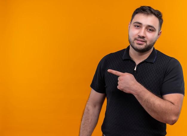 Junger bärtiger mann im schwarzen hemd, der mit zeigefinger zur seite zeigt, die kamera mit ernstem selbstbewusstem ausdruck betrachtet