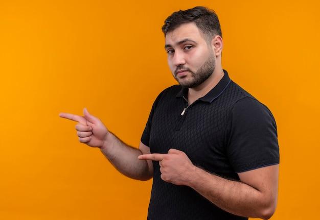 Junger bärtiger mann im schwarzen hemd, der mit zeigefingern auf die seite zeigt, die kamera mit ernstem selbstbewusstem ausdruck betrachtet