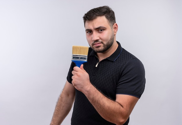 Junger bärtiger mann im schwarzen hemd, der pinsel hält kamera mit ernstem selbstbewusstem ausdruck betrachtet
