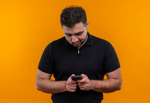 Junger bärtiger mann im schwarzen hemd, der smartphone hält, das mit jemandem plaudert