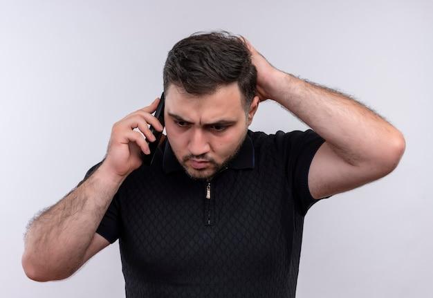 Junger bärtiger mann im schwarzen hemd, der verwirrt und sehr ängstlich schaut, während auf handy spricht