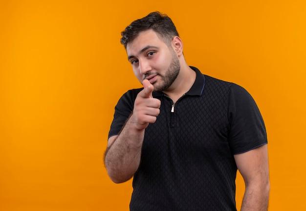 Junger bärtiger mann im schwarzen hemd, der zuversichtlich zeigt, mit zeigefinger zur kamera zu zeigen