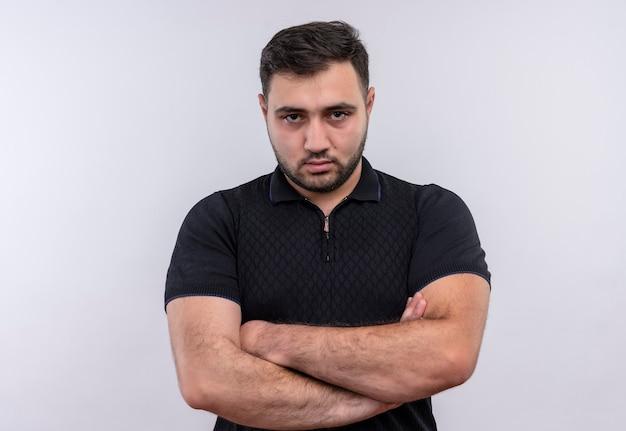 Junger bärtiger mann im schwarzen hemd mit verschränkten armen auf brust, die kamera mit stirnrunzelndem gesicht betrachten