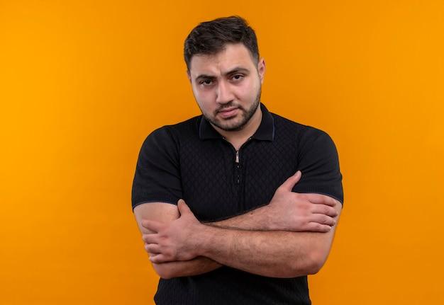 Junger bärtiger mann im schwarzen hemd syanding mit verschränkten armen auf brust mit stirnrunzelndem gesicht, das kamera betrachtet