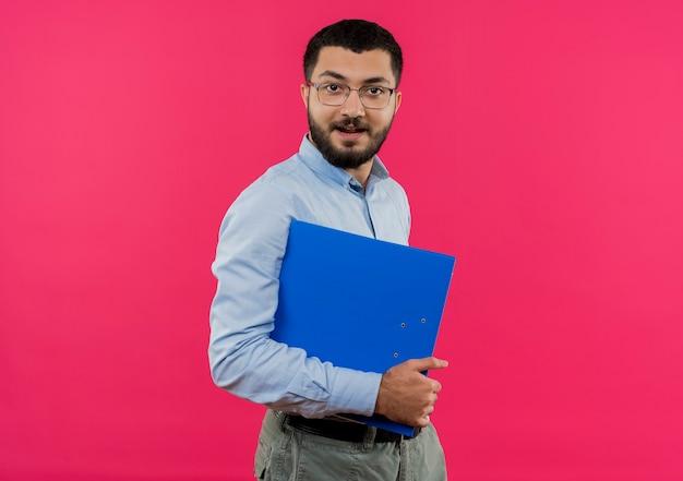 Junger bärtiger mann in den gläsern und im blauen hemd, die ordner mit lächeln auf gesicht halten
