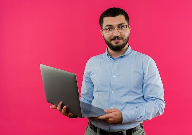 Junger bärtiger mann in den gläsern und im blauen hemd hält laptop, der zuversichtlich lächelt