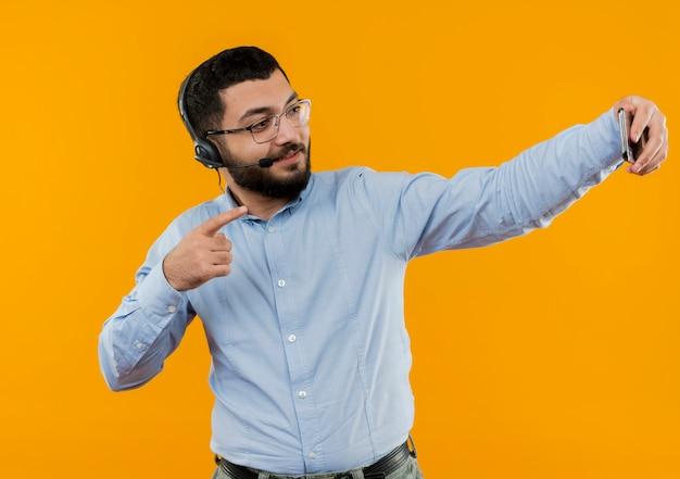 Junger bärtiger mann in den gläsern und im blauen hemd mit kopfhörern mit mikrofon, die selfie unter verwendung seines lächelnden smartphones tun