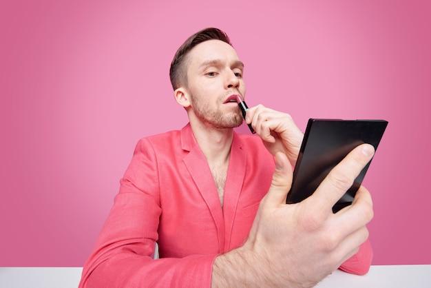 Junger bärtiger mann in der roten glamourösen jacke über haarigem torso, der lippenstift beim betrachten im spiegel anwendet