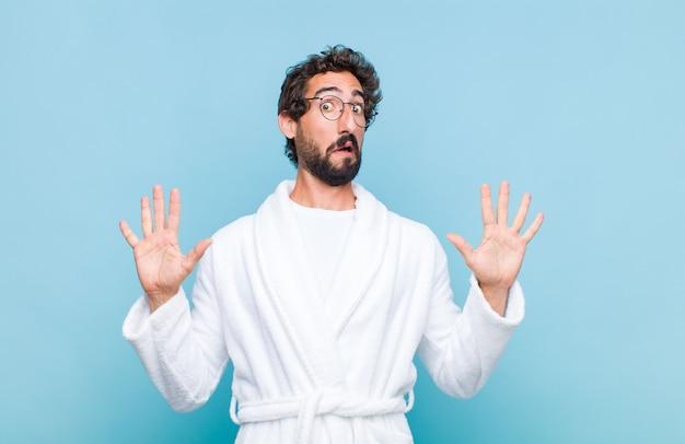 Junger bärtiger mann in einem bademantel, der sich betäubt und verängstigt fühlt und etwas erschreckendes fürchtet, mit offenen händen vorne, die sagen, bleib weg