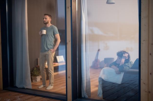 Junger bärtiger mann in freizeitkleidung, der etwas trinkt und durch ein großes fenster im wohnzimmer schaut, während seine frau sich auf der couch in der nähe entspannt?