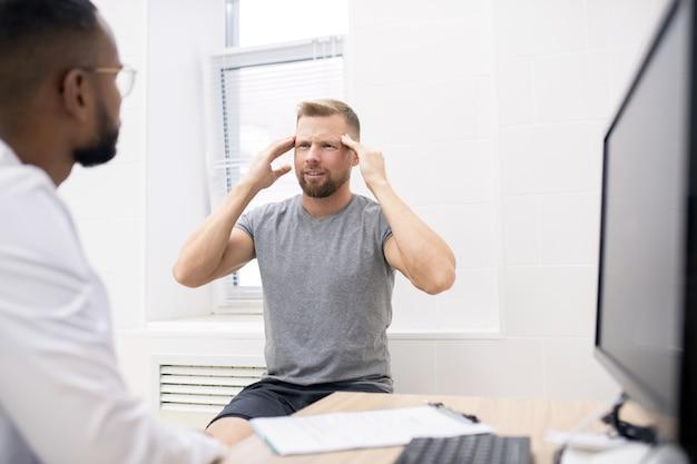 Junger bärtiger mann in freizeitkleidung, der seinen kopf berührt, während er sich über dauerhafte kopfschmerzen beim arzt in kliniken beschwert