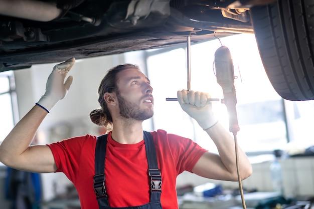 Junger bärtiger mann in schutzhandschuhen, der unter dem auto steht und seinen technischen zustand prüft