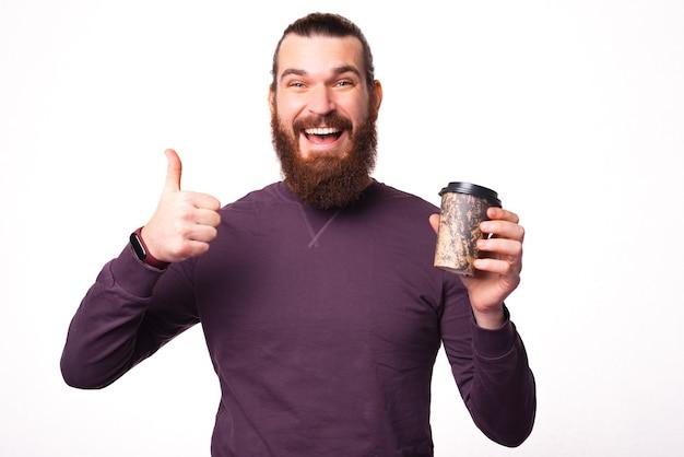 Junger bärtiger mann lächelt in die kamera und zeigt einen daumen hoch hält eine tasse heißes getränk