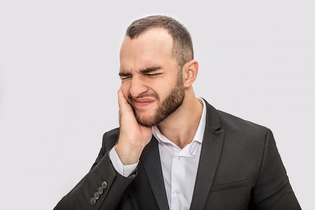 Junger bärtiger mann leiden unter zahnschmerzen. er hält die hand auf die wange und hält die augen geschlossen.