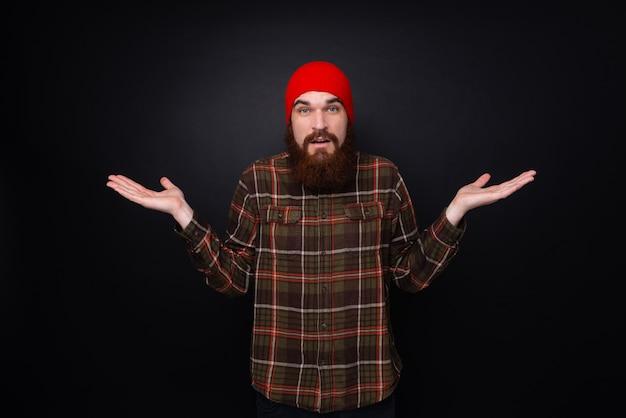 Junger bärtiger mann macht ich kenne keine geste. hipster, der roten wollhut auf schwarzem hintergrund trägt.