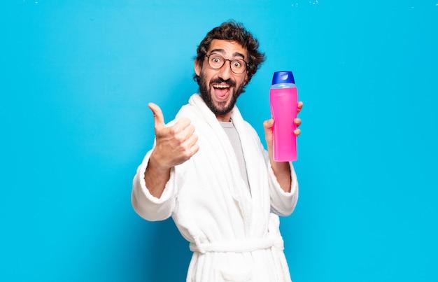 Junger bärtiger mann mit bademantel mit shampoo und schönheitsprodukten