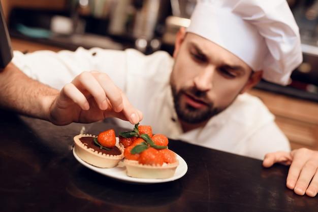 Junger bärtiger mann mit dem kuchen, der in der bäckerei steht