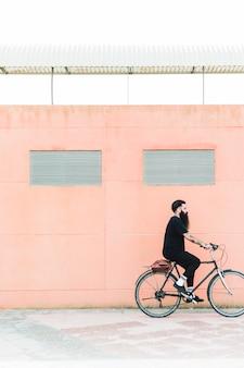 Junger bärtiger mann mit der umhängetasche, die ein fahrrad auf die stadtstraße reitet
