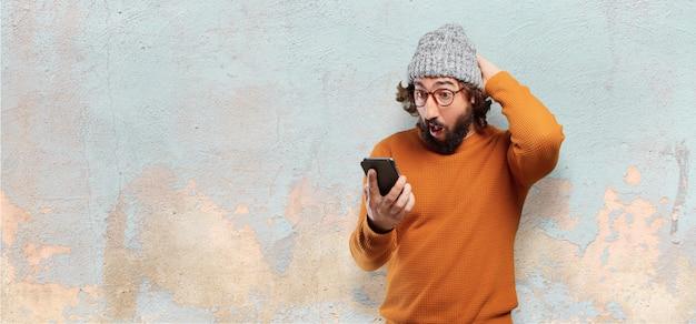 Junger bärtiger mann mit einem intelligenten telefon