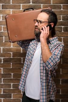 Junger bärtiger mann mit einem koffer auf seiner schulter.