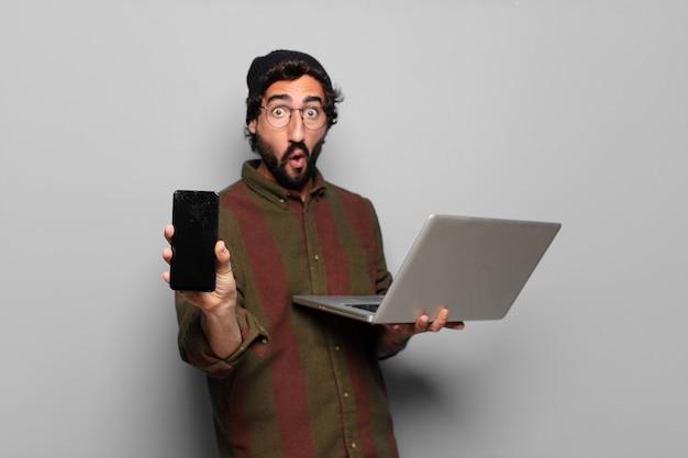 Junger bärtiger mann mit einem laptop