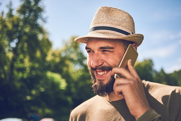 Junger bärtiger mann mit einem smartphone