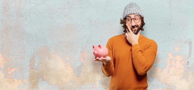 Junger bärtiger mann mit einem sparschwein