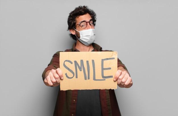 Junger bärtiger mann mit einer medizinischen maske und einem lächeln-konzeptbanner