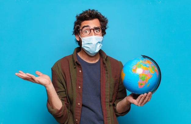 Junger bärtiger mann mit einer medizinischen maske und einem weltkartenmodell