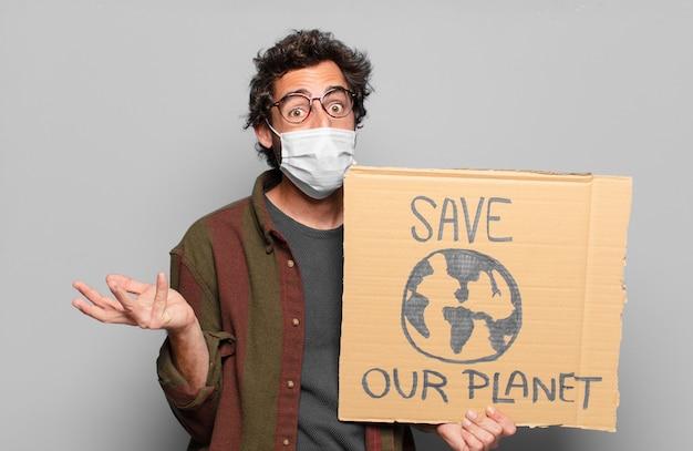 Junger bärtiger mann mit einer medizinischen maske und retten sie unser planetenbanner