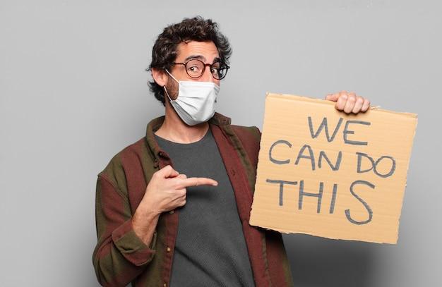 Junger bärtiger mann mit einer medizinischen maske und wir können dieses konzept tun