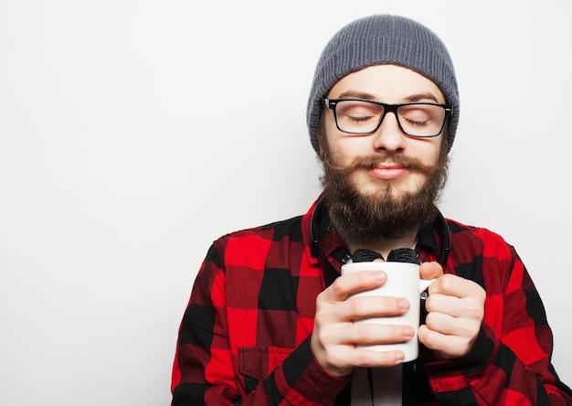 Junger bärtiger mann mit einer tasse kaffee auf grau
