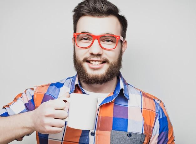 Junger bärtiger mann mit einer tasse kaffee
