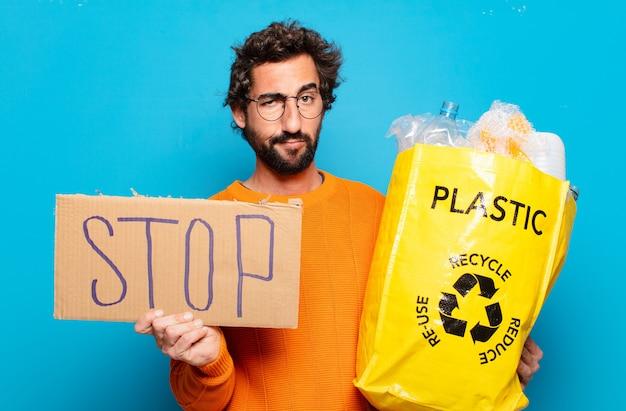 Junger bärtiger mann mit plastik zum recycling und stopptafel