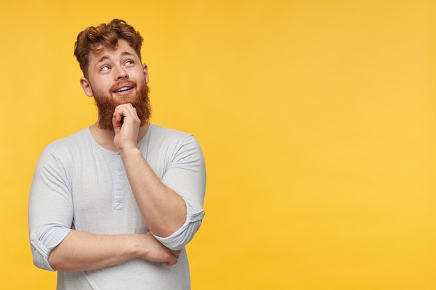 Junger bärtiger mann mit roten haaren, trägt ein leeres t-shirt, schaut nachdenklich und glücklich zur seite und berührt sein kinn auf gelb.