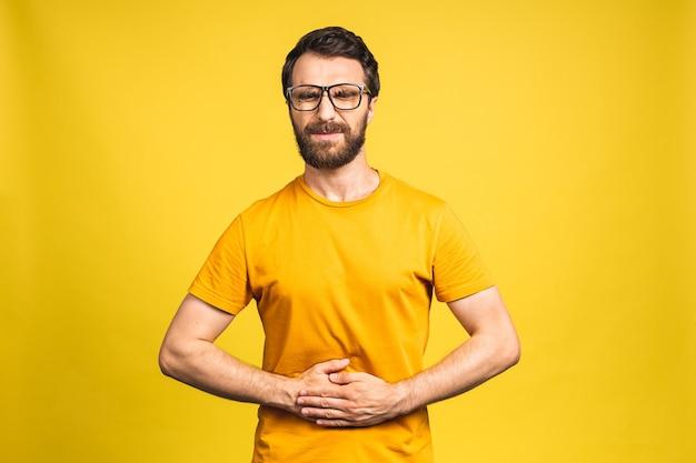 Junger bärtiger mann mit schmerzen, der seinen schmerzenden magen auf gelbem hintergrund hält. bauchschmerzen.