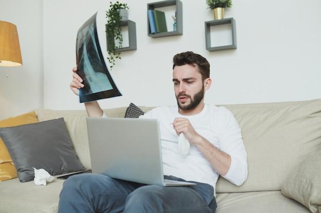 Junger bärtiger mann mit taschentuch und lungenröntgenergebnis, das auf couch vor laptop sitzt und mit online-arzt zu hause berät