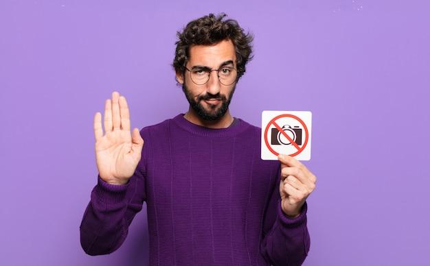 Junger bärtiger mann mit verbotenem fotozeichen