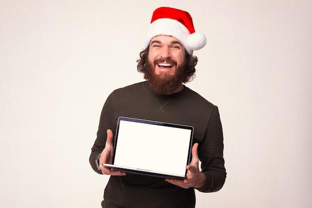 Junger bärtiger mann mit weihnachtsmütze hält seinen laptop und zeigt der kamera den bildschirm.